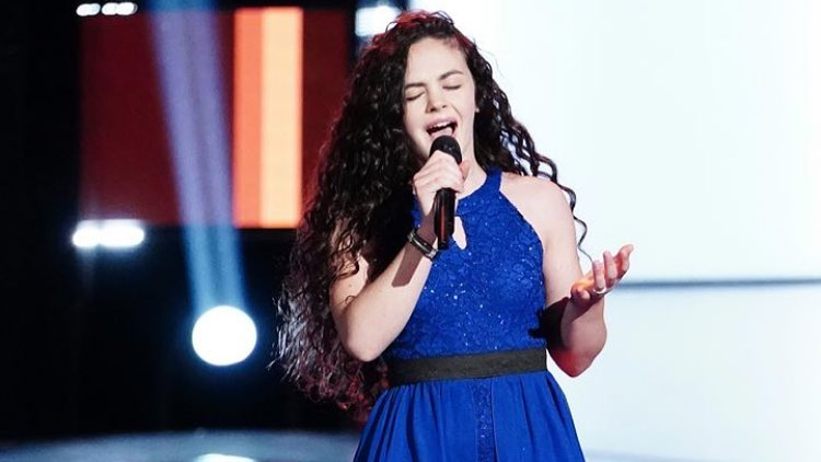 Chevel is holding a mic on her right hand wearing a blue dress