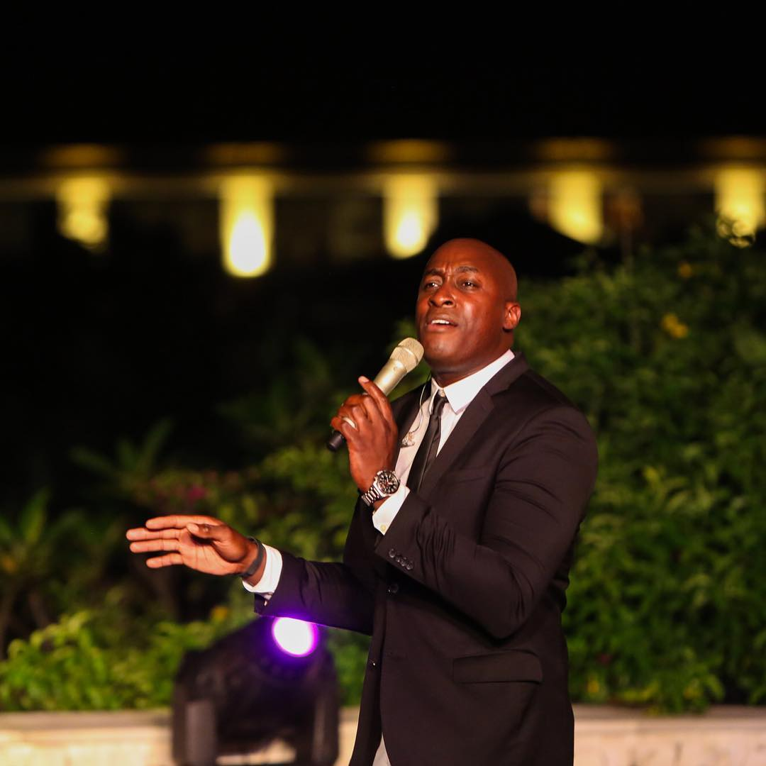 Jermaine Paul wearing a black suit and a white shirt holding a mic on his left hand