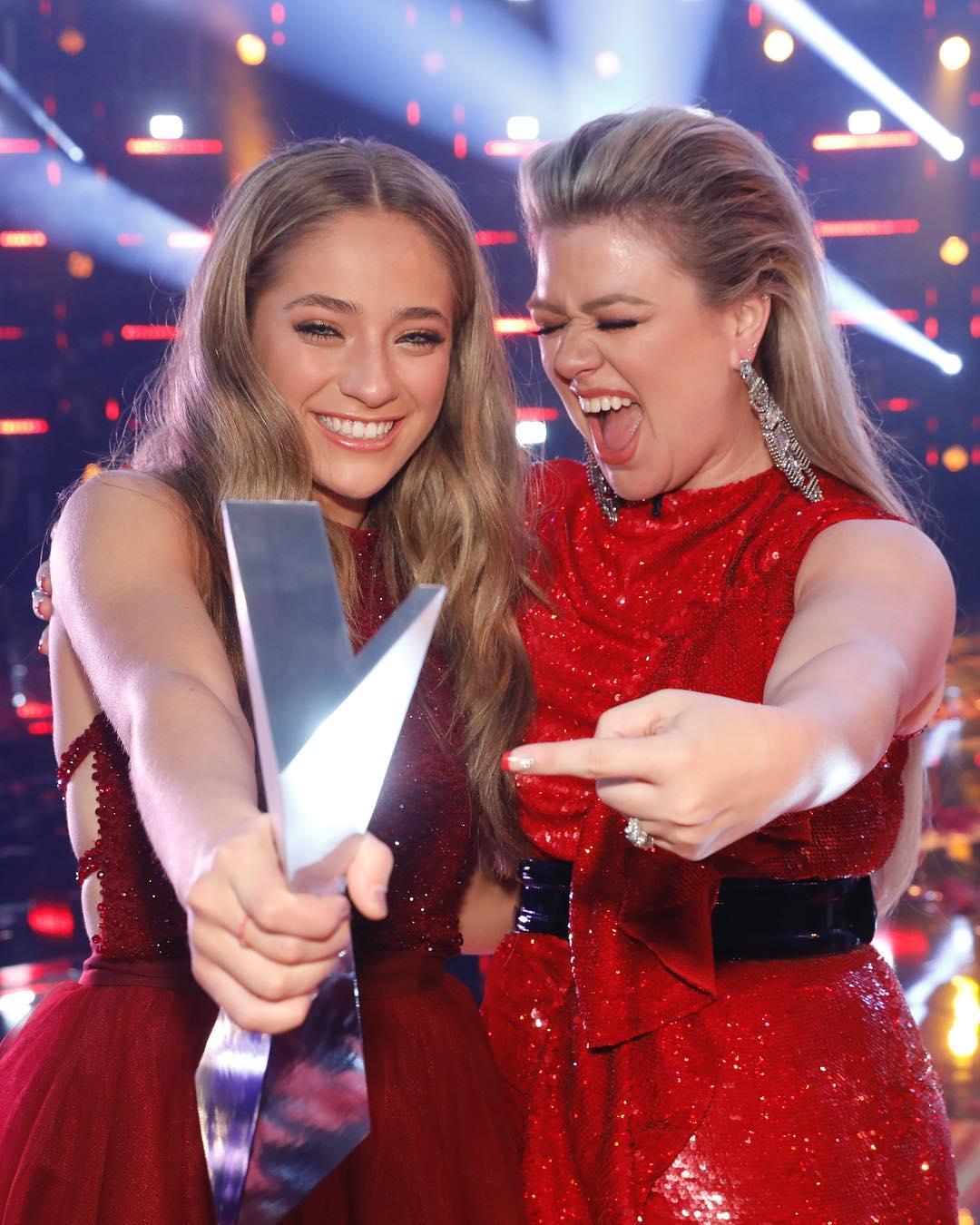 Brynn Cartelli holding her the voice trophy while her coach Kelly Clarkson is pointing at the award