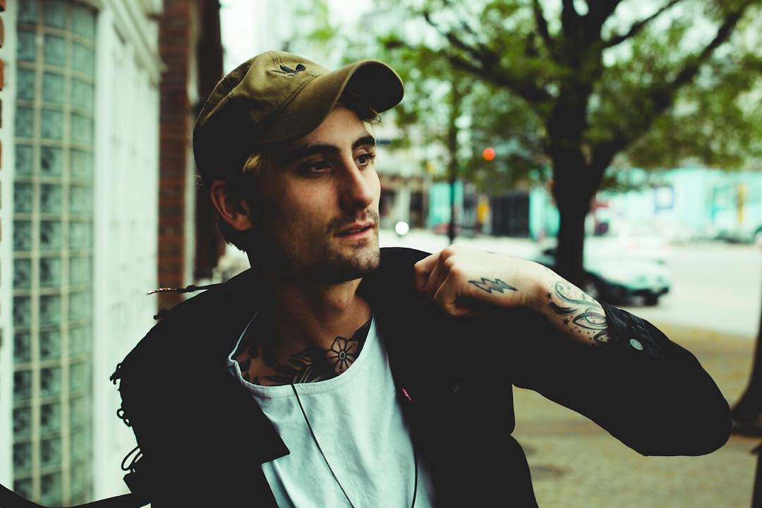 Kyle Pavone is wearing a grey hat, a white t-shirt and a black jacket