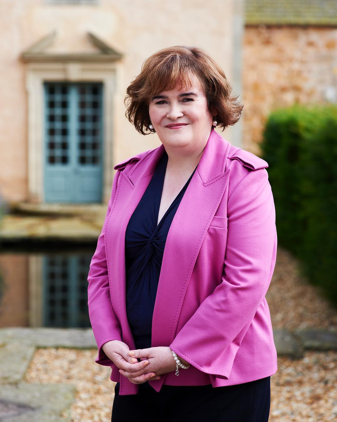 Susan Boyle wearing pink outer and a subtle smile on her face