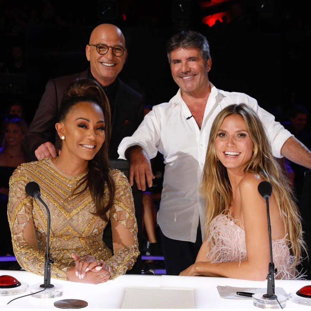 Heidi Klum and Mel B are sitting on the chair on the set of AGT while Simon Cowell and Howie Mandel are standing behind them