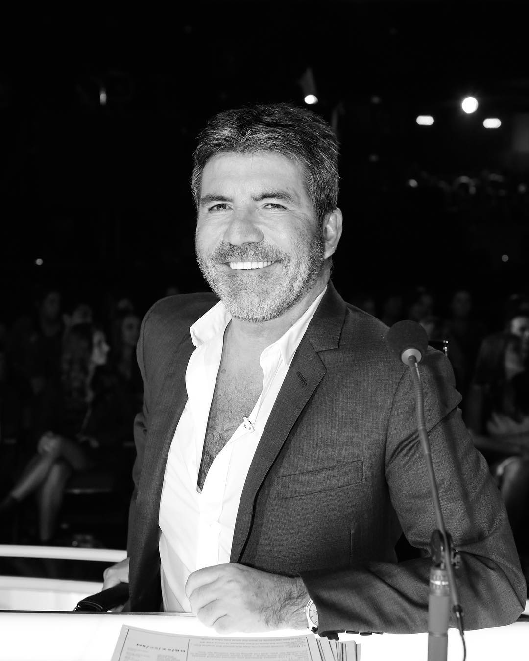 Simon Cowell sitting on a chair on the set the of AGT