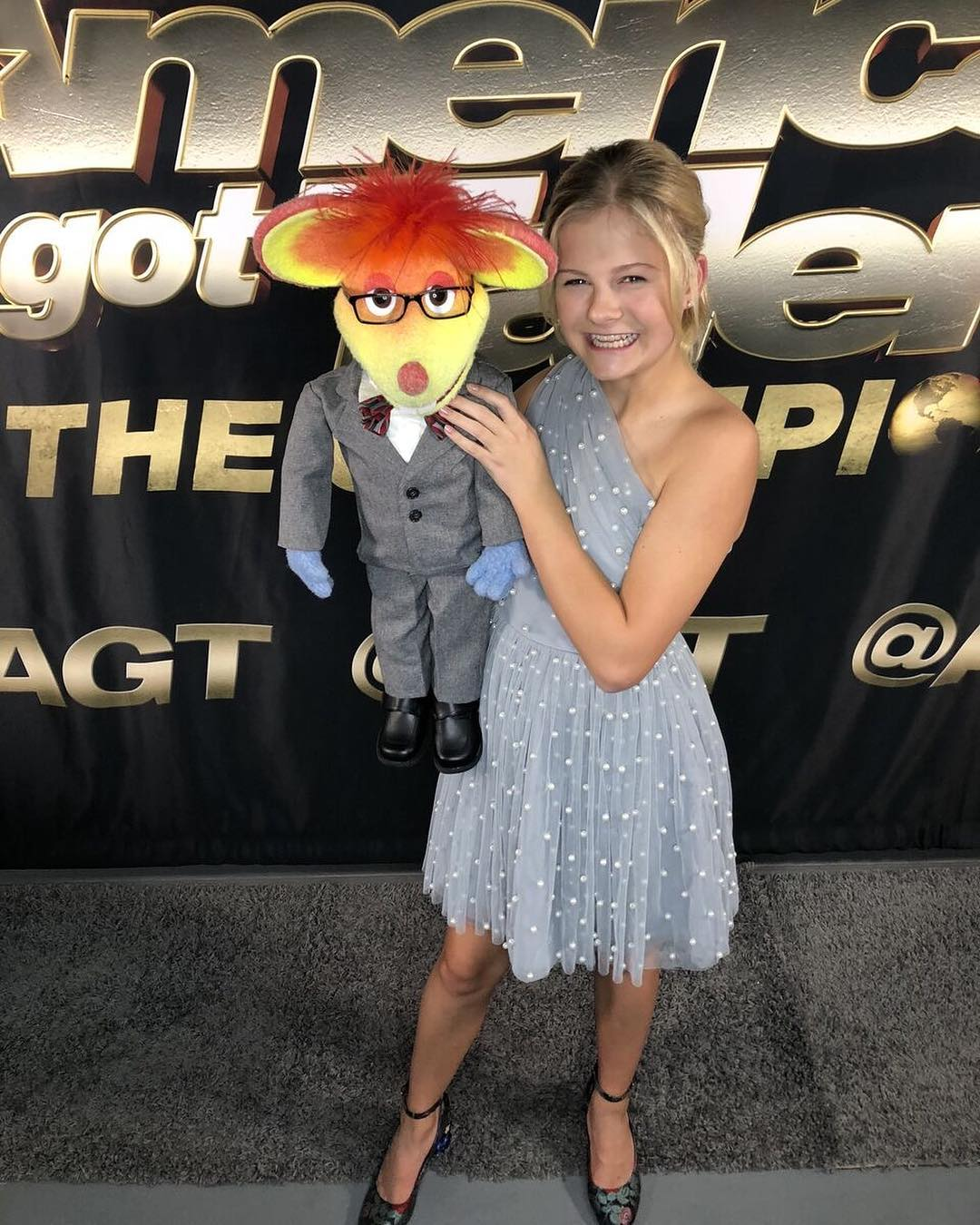 Darci Lynne Farmer standing on the set of AGT: The Champions holding her mouse poppet in her hand