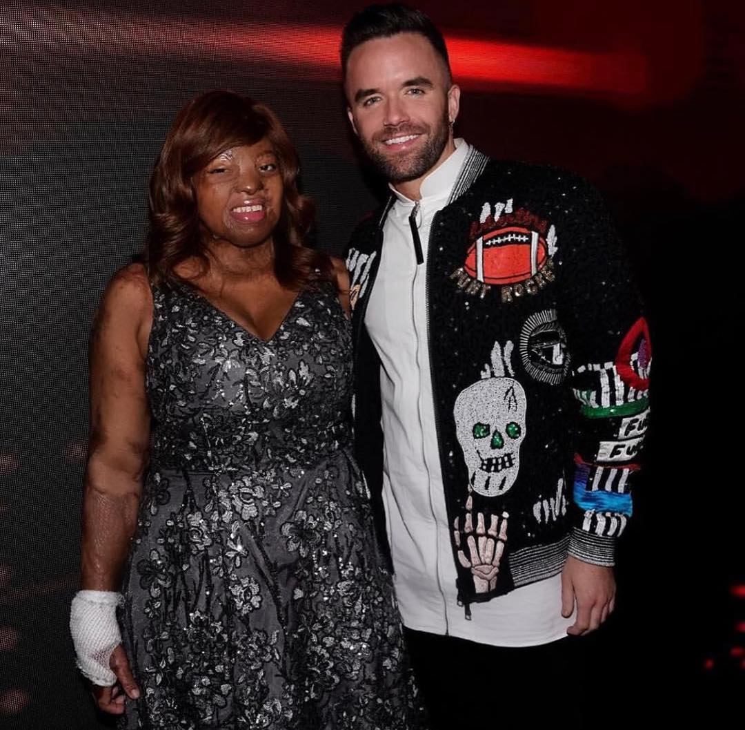 Brian Justin Crum standing alongside Kechi Okwuchi with smile on his face