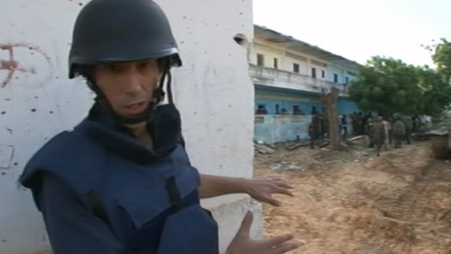 The presenter reports from a battlefield, wearing full body armor