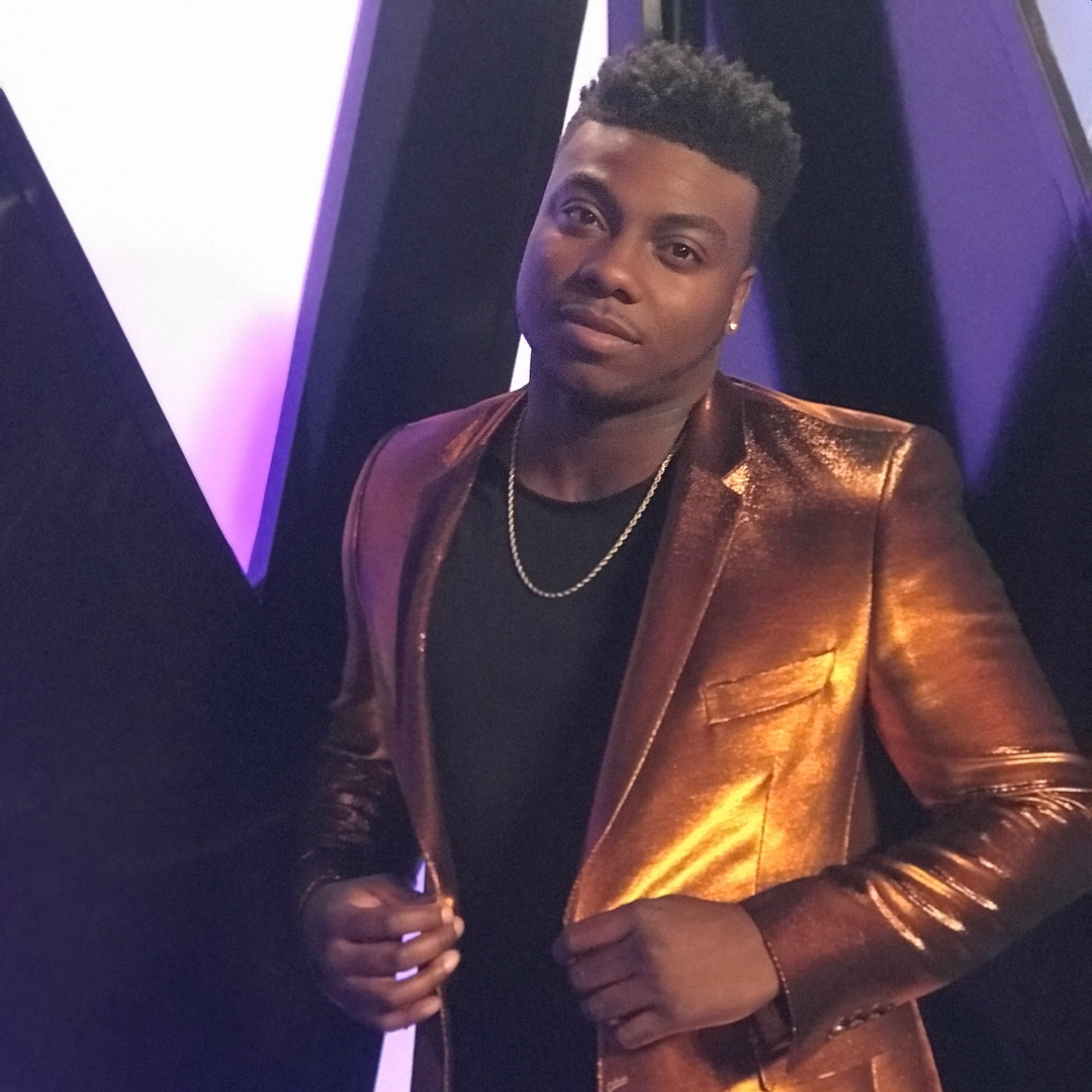 Kirk Jay wearing a golden colored suit