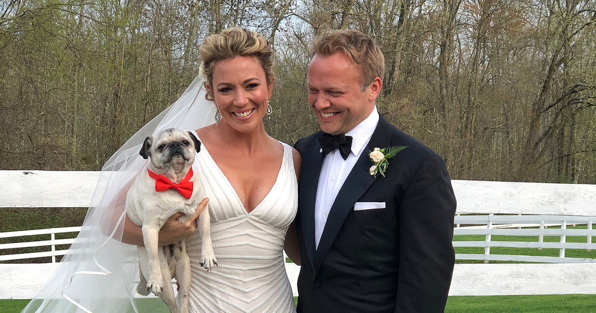 Brooke and her groom pose in their wedding day. Brooke is also holding her pet Pug