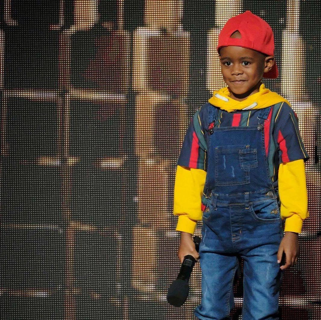 DJ Arch Jnr holding mic in his right hand on the stage of AGT: The Champions