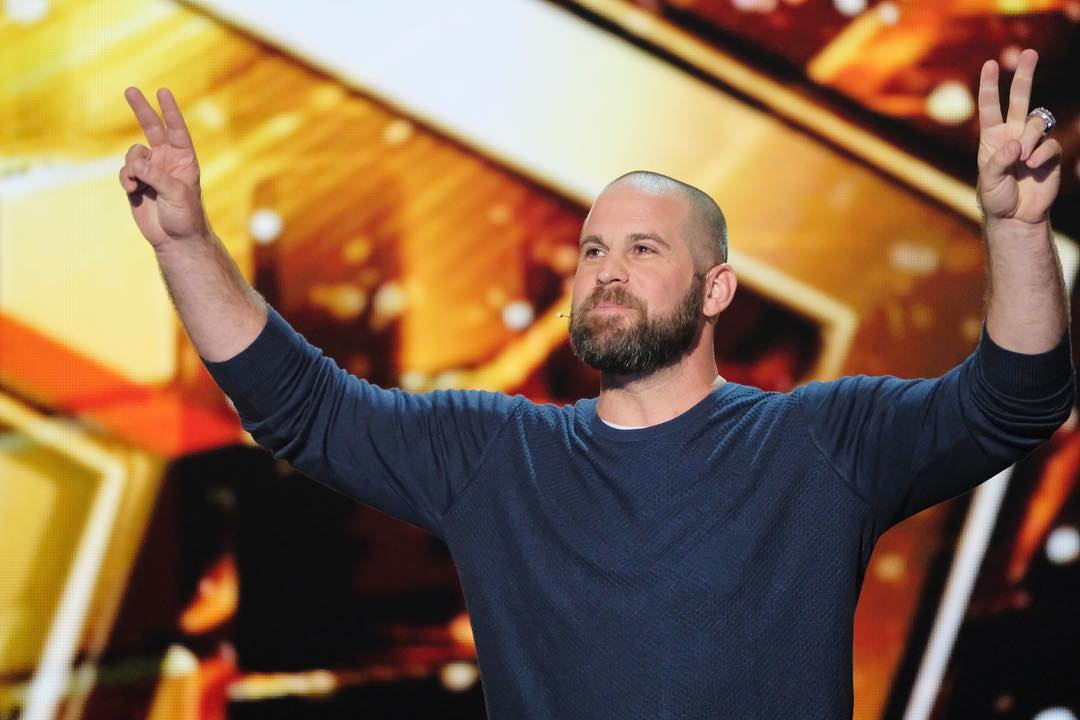 Jon Dorenbos with his signature peace out pose on the stage of America's Got Talent: The Champions stage