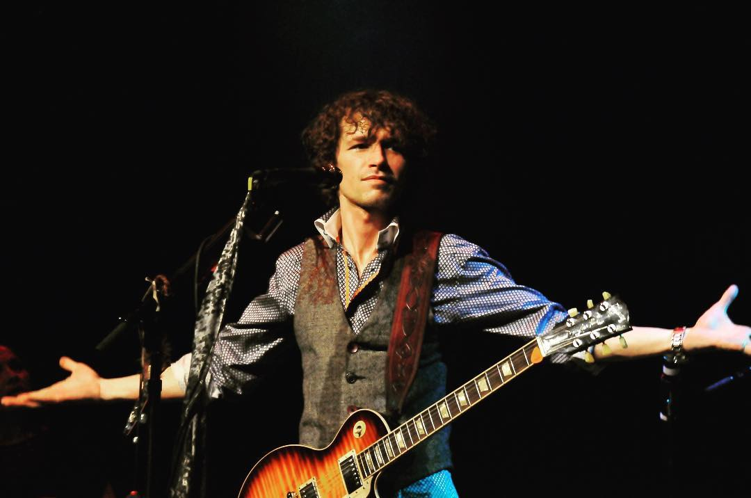 Michael Grimm holding a guitar on his shoulder and standing with open arms