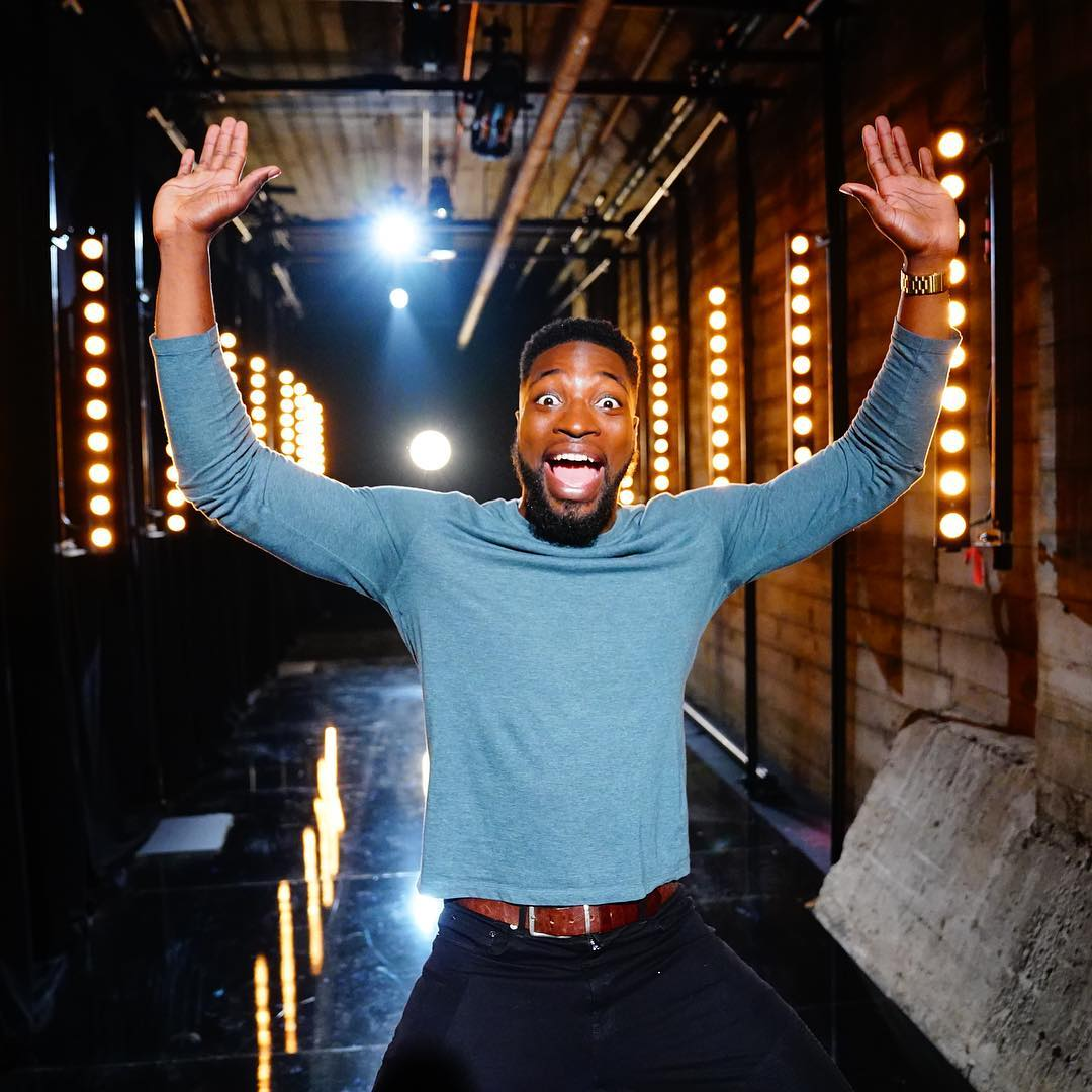 Preacher Lawson standing with open mouth and his hands in the air