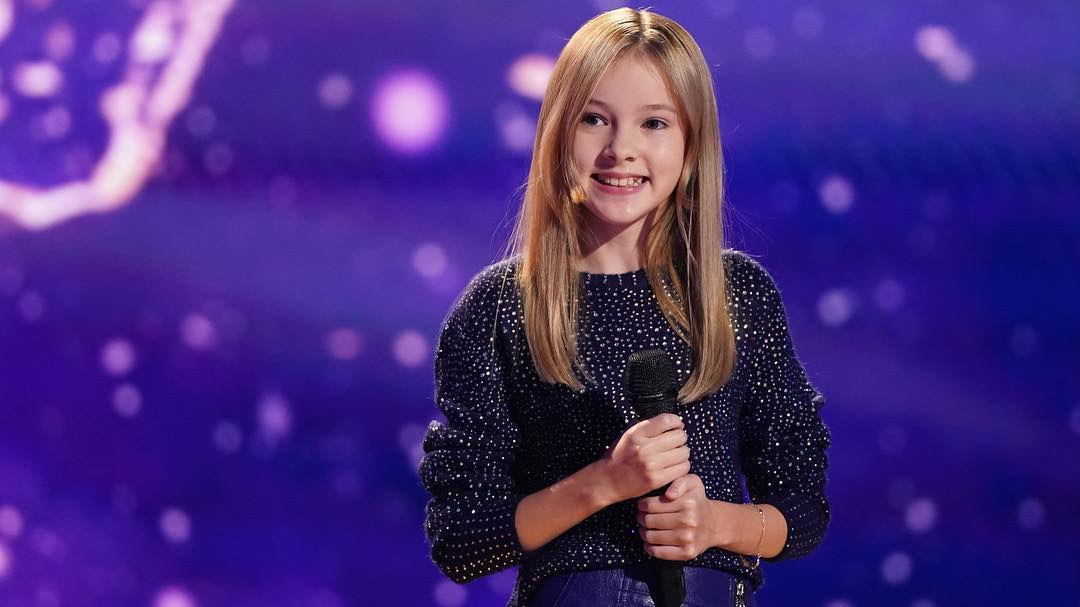 Daneliya Tuleshova holding a mic in her hands on the stage of The World's Best