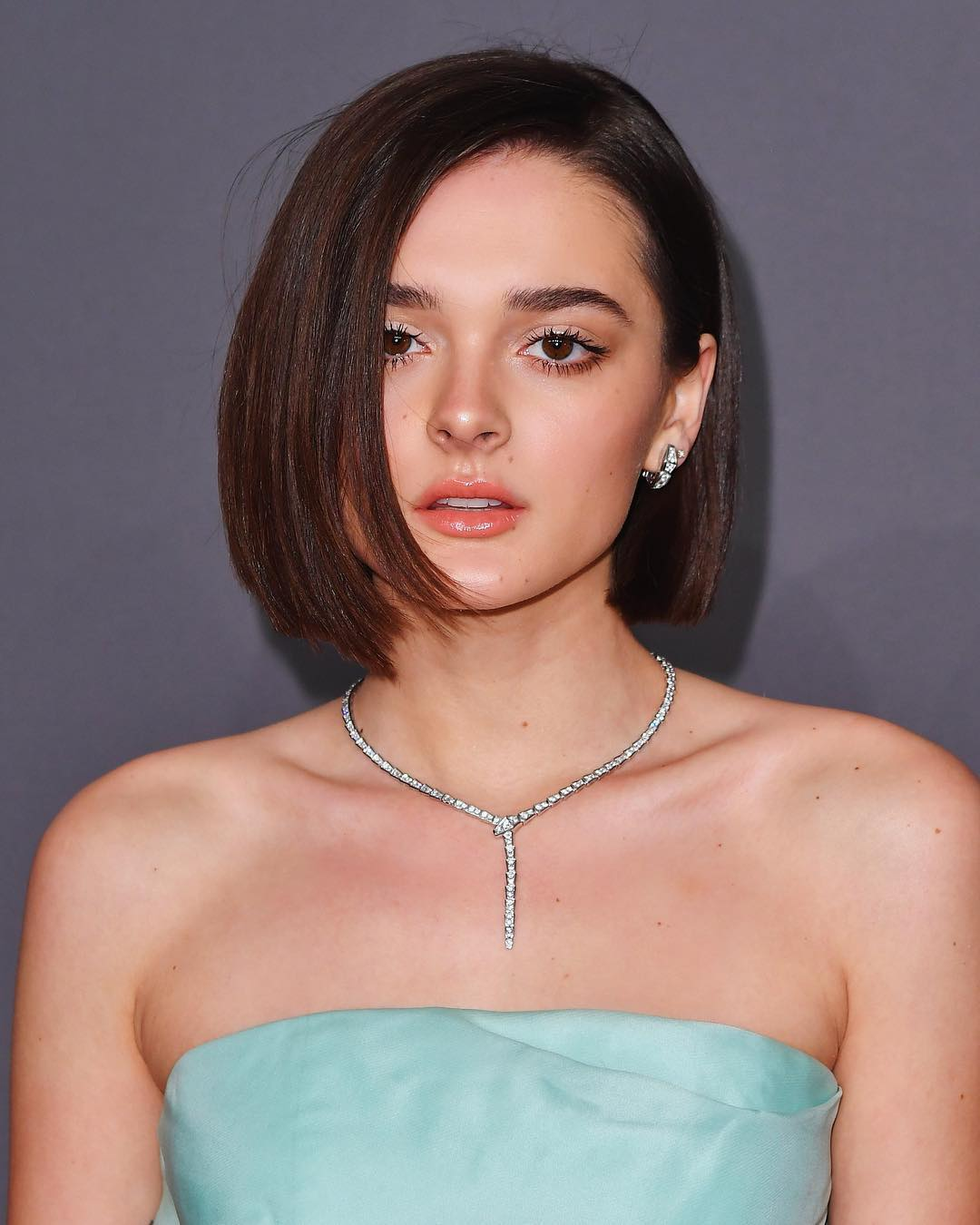 Charlotte Lawrence is wearing an elegant neck-piece and a light green tube dress