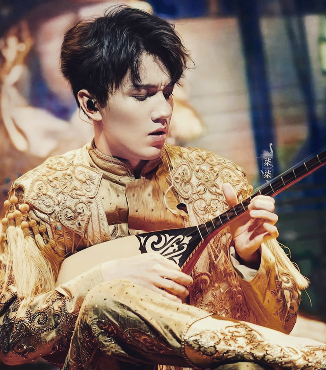 Dimash Kudaibergen holding oud in his hands while wearing golden colored attire