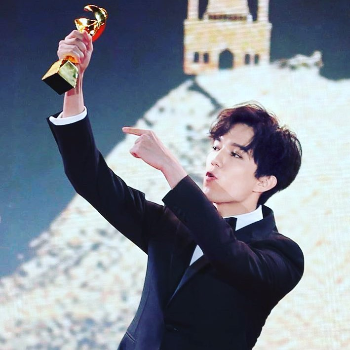 Dimash Kudaibergen holding a trophy in his right hand
