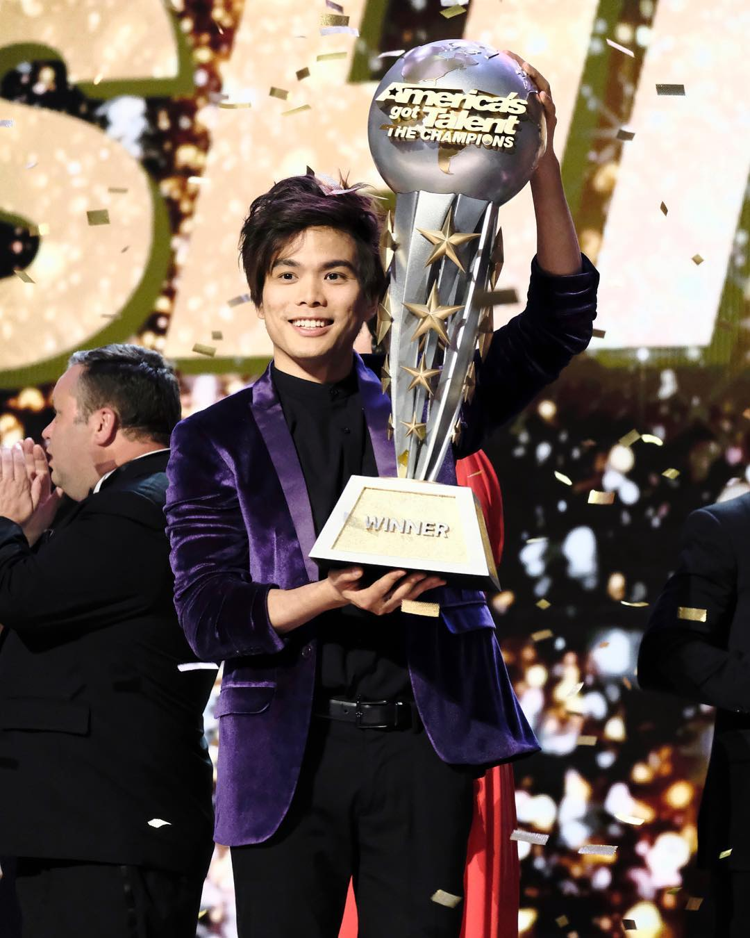 Shin Lim holding his America's Got Talent: The Champions trophy