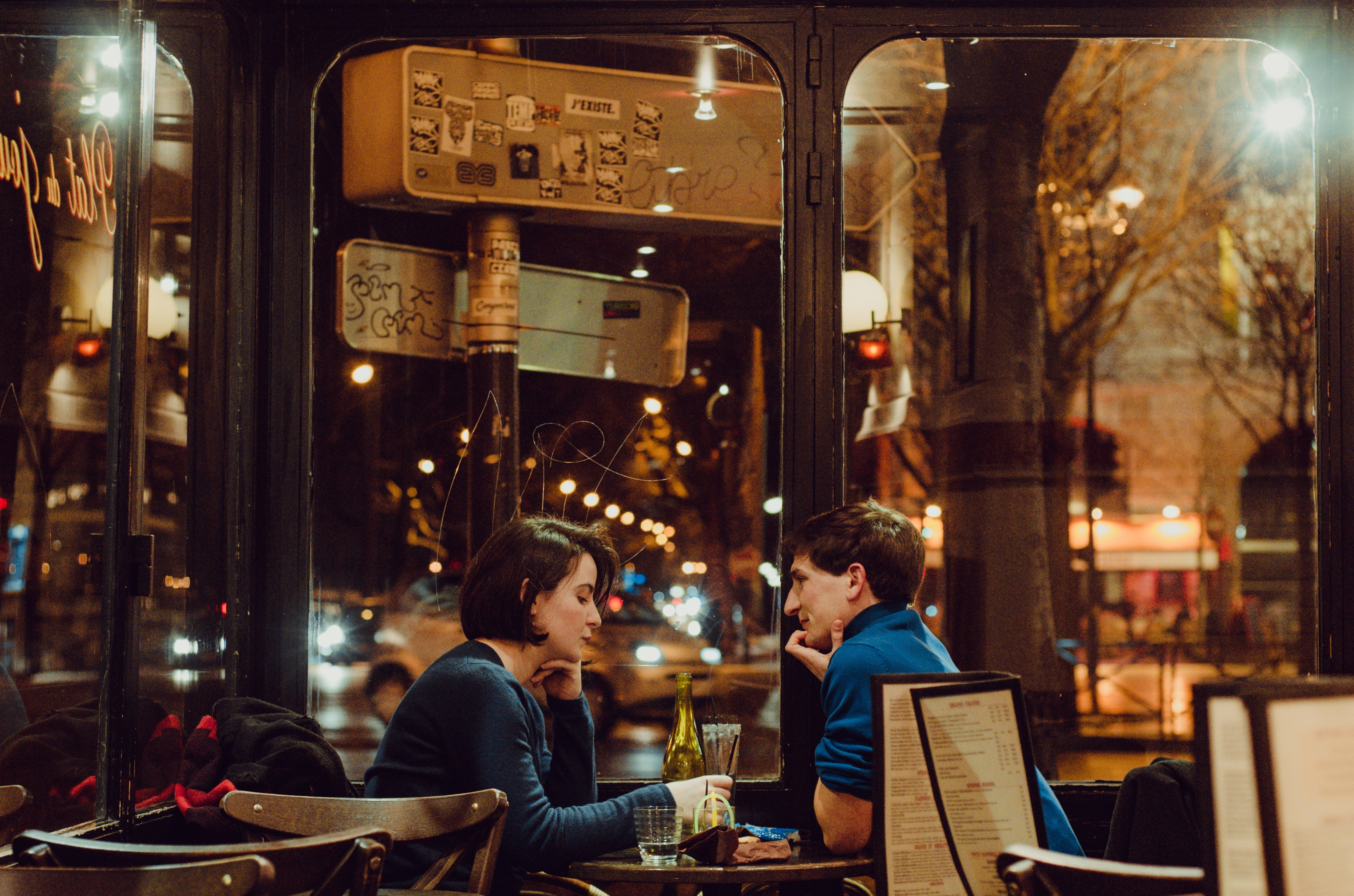 A girl and a guy on a date in a street side cafe in the night.