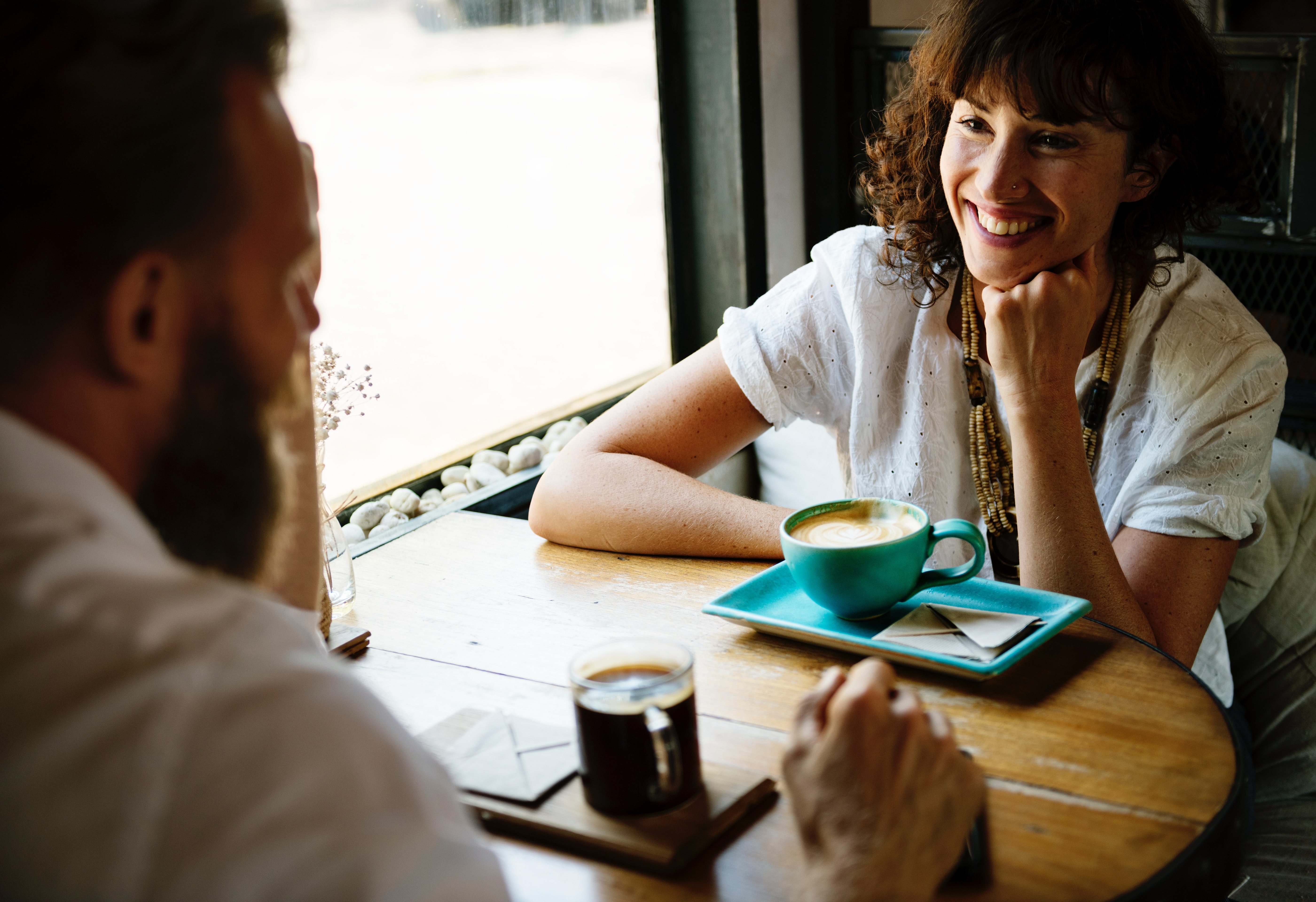 A guy and a girl sit on a window side seat on a coffee date on a cafe.