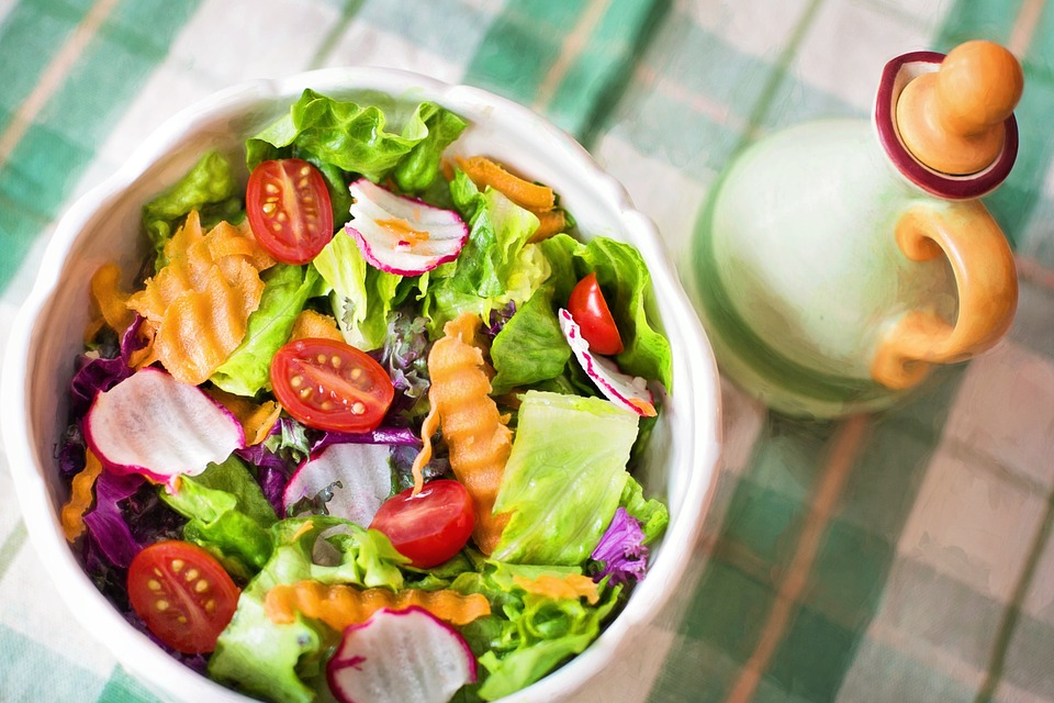 A bowl full of salad, containing cabbages, tomatoes, radishes etc