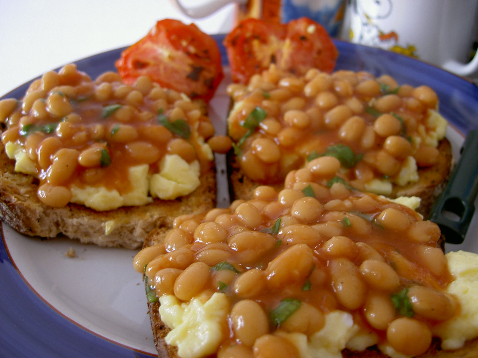 Baked beans and eggs presented beautifully on a toast.
